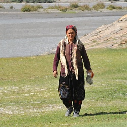 woman walking by Oxus river with Afghanistan in the background
